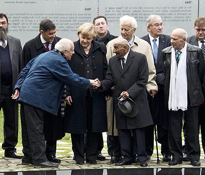 קרוון לוחץ את ידו של ניצול המחנות ריינהרד פלוריאן (צילום: AFP)