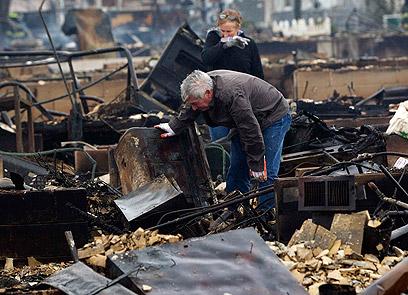 תושב קווינס בודק את הריסות ביתו שעלה באש (צילום: רויטרס)