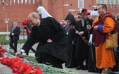 """פוטין מניח פרחים בכיכר האדומה. """"מתח שריר"""" (צילום: MCT)"""