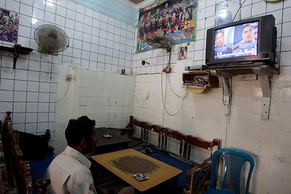 עיראקי צופה בסיקור הבחירות   (צילום: AFP)