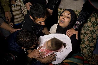 תינוקת שנהרגה בתקיפה בעזה. לטענת הפלסטינים, 16 אזרחים נהרגו עד כה ברצועה (צילום: AP)