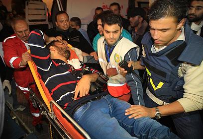 פינוי צלם עיתונות שנפצע בתקיפה הלילה (צילום: AFP)