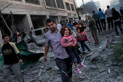 בורחים מבתיהם לאחר הפצצת האצטדיון בעזה היום (צילום: AP)