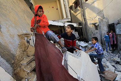 ילדים בעזה על הריסת מבנה שהותקף (צילום: AFP)