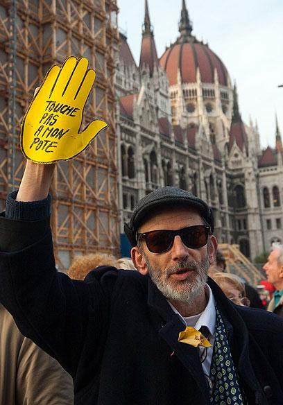 """""""אל תגעו בחבר שלי"""". מפגין על רקע הפרלמנט (צילום: AFP)"""
