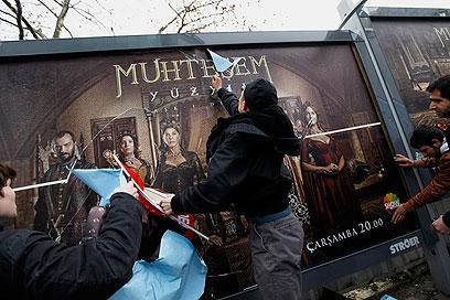 מתנגדים מנסים להסיר את כרזות הפרסומת (צילום: רויטרס)