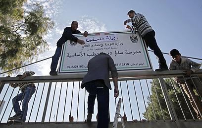 """מחליפים שלט לבית ספר עם הכותרת """"מדינת פלסטין"""" (צילום: AFP)"""
