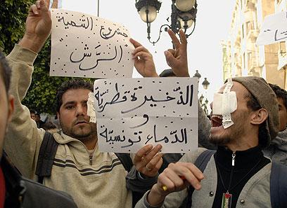 """הפגנת הזדהות בתוניסיה. """"יכולים לקחת את עינינו, אבל לא את קולנו"""" (צילום: AP)"""