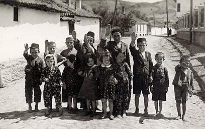 בתמונה זו נראים חיילים גרמנים כופים על ילדים יהודים להצדיע להם במועל יד. הילדים מחייכים, אולי בלית ברירה, ונראה שאינם מבינים שהפכו לכלי משחק בידיהם של חיילים שאיבדו צלם אנוש