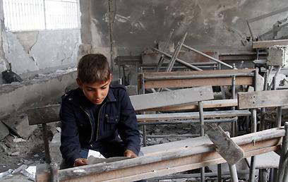ילד בבית ספר שנפגע בהתקפות צבא אסד בחלב (ארכיון) (צילום: AP)