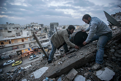 אוספים את השברים בעיר חלב (צילום: AP)