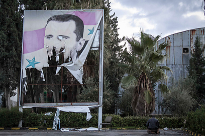 הסוף קרוב? מורדים תולשים כרזה של אסד (צילום: AP)