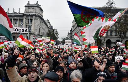 דגל צועני מונף בהפגנה נגד אנטישמיות בהונגריה (צילום: EPA)