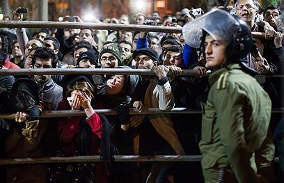 """צופים במעמד ההוצאה להורג. נשים קראו: """"רחמו עליהם"""" (צילום: AP)"""