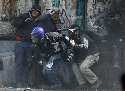 תופסים מחסה במהלך המהומות (צילום: רויטרס)