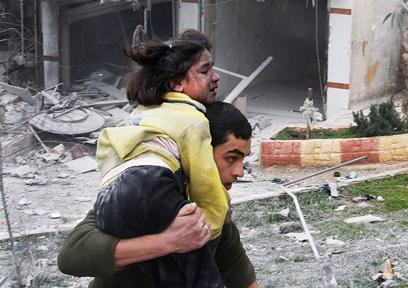 אח נושא את אחותו לאחר הפצצה בחלב (צילום: AP)