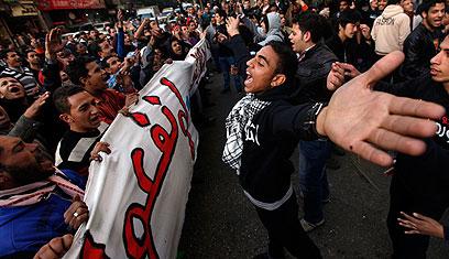מפגינים צועדים בכיכר תחריר (צילום: רויטרס)