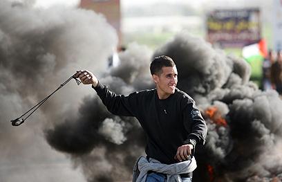 פלסטיני מיידה אבן בחברון, היום (צילום: AFP)