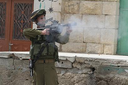 """לוחם צה""""ל יורה רימוני גז עם הרינגו  (צילום: גיל יוחנן)"""