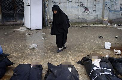"""גופות בעיר חלב. """"דרוש כוח ערבי בקסדות כחולות""""  (צילום: AFP)"""