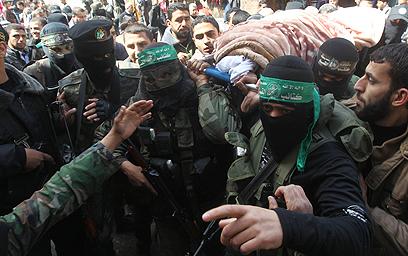לוחמי חמאס נושאים את גופתה של פרחאת (צילום: AFP)