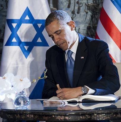 אובמה כותב בספר האורחים (צילום: AFP)