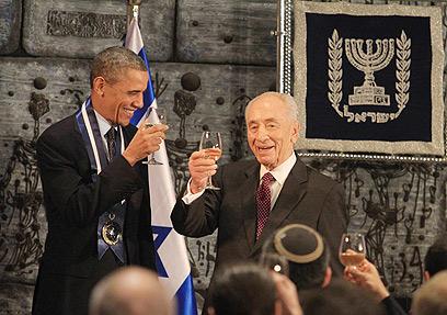 """""""עד 120"""" בעברית. אובמה ופרס מרימים כוס (צילום: גיל יוחנן)"""