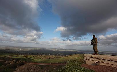 חיילי ישראלי צופה על צדו הסורי של הגבול (צילום: EPA)