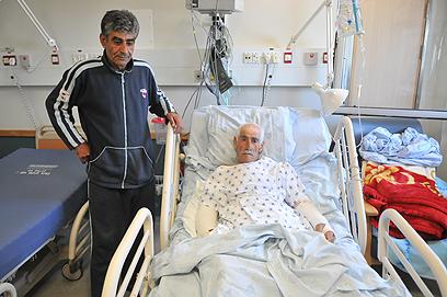 """""""לא תהיה יותר מאנרכיה"""". חוסני ברהוש ואביו בבית החולים (צילום: ירון ברנר)"""