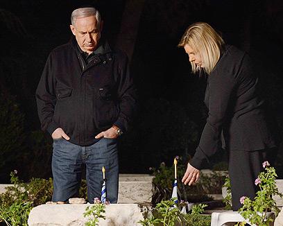 """ראש הממשלה ורעייתו במוצאי שבת ליד קברו של יוני נתניהו  (צילום: קובי גדעון, לע""""מ)"""