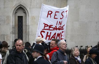 """""""נוחי על משכבך בבושה"""". שלט מחאה במסע ההלוויה (צילום: AFP)"""