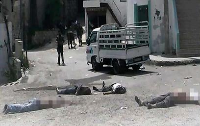 """הגופות שנמצאו שלשום בעיירה ביידה. """"נשים וילדים"""" (צילום: AP)"""