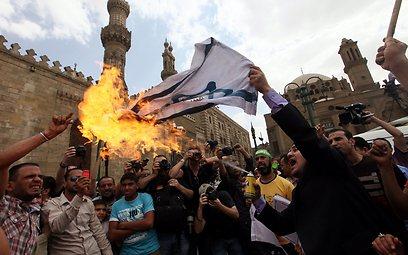מעלים באש את דגל ישראל, היום בקהיר (צילום: EPA)