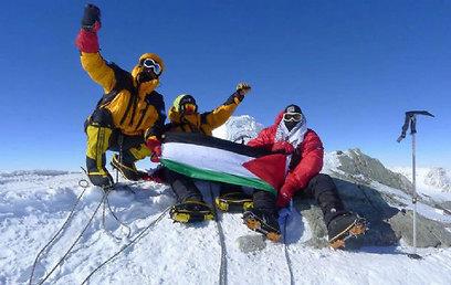 קבוצת המטפסים ודגל פלסטין על פסגת ההר