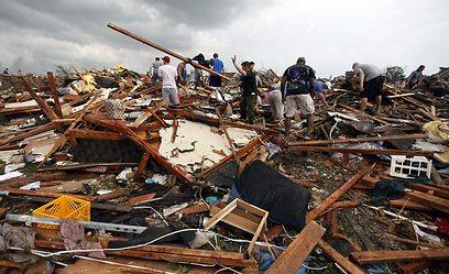תושבים בעיירה מור בין ההריסות  (צילום: AP)