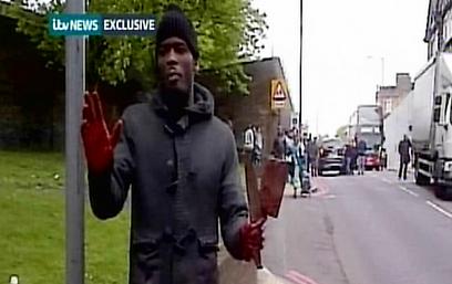 """הסרטון ששודר בבריטניה, ידיים מגואלות בדם: """"זה עונש עין תחת עין"""" (צילום: רויטרס)"""
