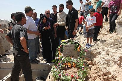 בני המשפחה ליד הקבר (צילום: גיל יוחנן)