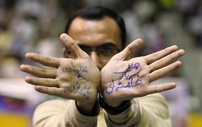 """רוב המועמדים מקורבים להנהגה. תומך של """"סעיד ג'לילי חייל של חמינאי"""" (צילום: AFP)"""