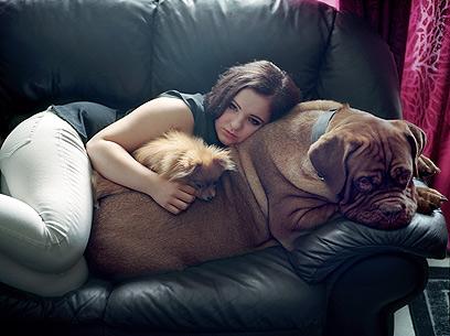 """איזלין רוז, בת 15. הסתתרה מאחורי סלע. """"אחרי אוטויה היה לי קשה לישון. פחדתי מהחושך וסבלתי מסיוטים נוראיים. אימא שלי ואני החלטנו שכלב יכול לעזור לי, אז קיבלתי את אתנה. עכשיו היא ישנה על הבטן שלי כל לילה"""" (צילום: Andrea Gjestvang /MOMENT)"""
