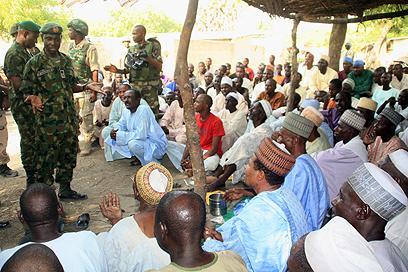 חיילים מדברים עם כפריים על ההצטרפות לבוקו חראם (צילום : AFP PHOTO / NIGERIAN MILITARY)