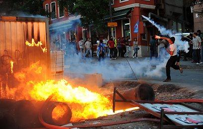 העימותים באיסטנבול. יידו אבנים והבעירו פחים (צילום: AFP)