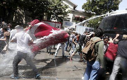 תותחי המים של המשטרה מול הדגל הטורקי של המפגינים (צילום: EPA)