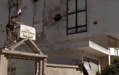 חייל סורי קובע את דגל המדינה על בניין בקוסייר, אתמול (צילום: רויטרס)