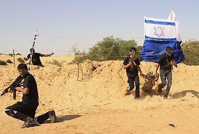 """ילדים חוטפים """"חייל"""" ממוצב מדומה של ישראל (צילום: AFP)"""