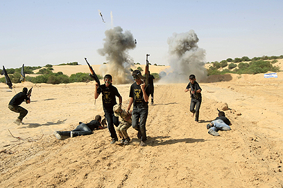 """""""החטוף"""" נלקח כפות בעוד החברים מחפים באש (צילום: AFP)"""