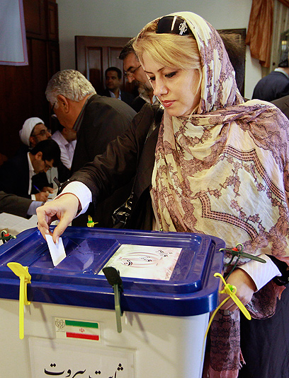אישה איראנית משלשלת את הפתק שלה לקלפי (צילום: AP)