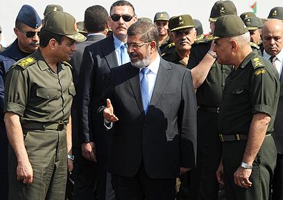 יחסים מעורערים. מורסי וראשי צבאו, בהם מפקד הצבא א-סיסי (משמאל) (צילום: AP)