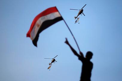הצבא התייצב לצד העם. מסוקים נושאים את דגלי מצרים מעל שמי קהיר (צילום: רויטרס)