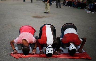 """הפיכה ססגונית: מפגינים במסיכות """"אנונימוס"""" ובאיפור גוף (צילום: רויטרס)"""