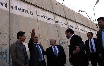 בלאטר ורג'וב על רקע גדר ההפרדה (צילום: EPA)